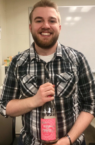 Andrew smiling with signed bottle